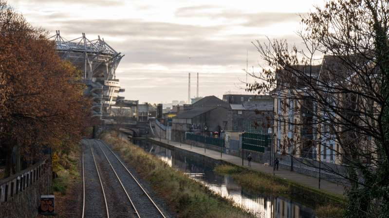 a large long train on a railroad track: File photo. Exterior of Croke Park on the left.